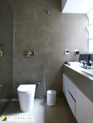 Banheiro revestido com massa cimentícia da NSBrasil. O espelho foi instalado na frente de um dos vãos da janela, já que a configuração original do ap era o local da lavanderia.
