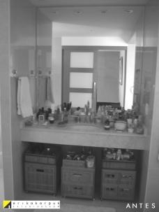 Área do lavatório ANTES. Encaixado entre duas paredes e a iluminação mal dimensionada, impedia a moradora de se maquiar no local. Pouco espaço de armazenamento. Projeto Erika Karpuk
